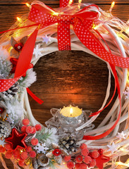 Candle with Christmas wreath and Christmas lights on a wooden background.
