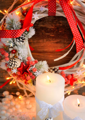 White candles on the snow with Christmas wreath and Christmas lights.