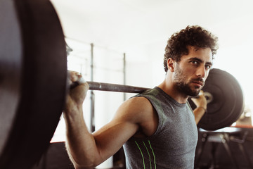 Bodybuilder working out at gym with heavy weights