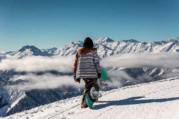 Back view of snowboarder standing on the background of mountains