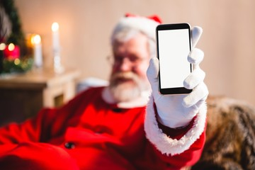 Santa claus sitting and showing his smartphone