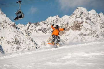 Male snowboarder jumping on the mountain slope