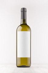 Green wine bottle with blank white label on white wooden board, mock up, vertical. Template for advertising, design, branding identity.
