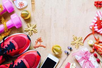 Fitness, healthy and active lifestyles love concept, dumbbells, sport shoes, skipping rope or jump rope and smart phone with Christmas decoration items on wood background.