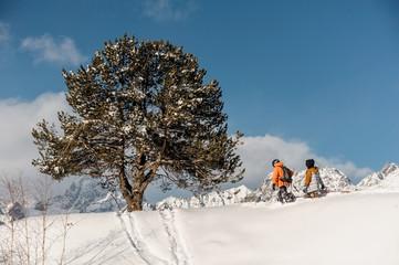 Couple of snowboarders in sportswear climbing the mountain