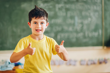 Happy child working in classroom, big thumbs up, education, back to school concept