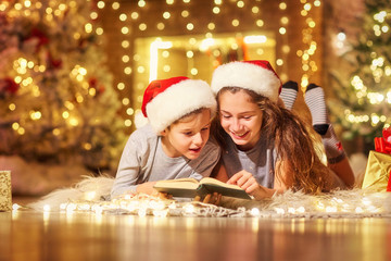 Two children on the floor read a book in a room decorated with Christmas decorations.
