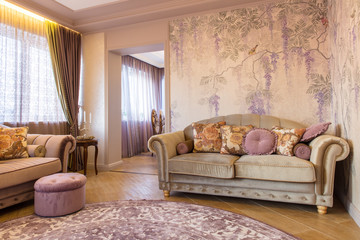 Living room with soft sofa, wallpaper with grapes and purple carpet