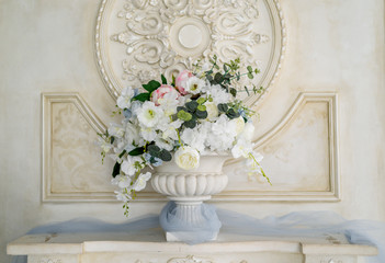 Artificial bouquet of flowers in white antique vase near wall in the interior, free space