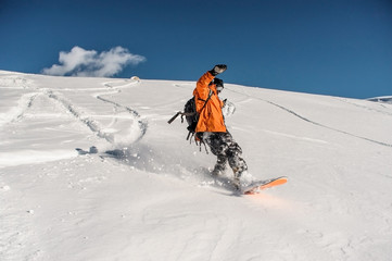 Snowboarder riding on the beautiful snow slope