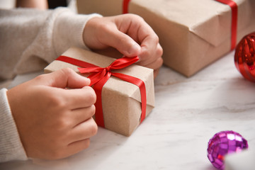 Kid hands wrapping a brown present box.
