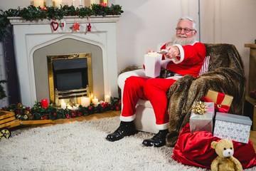 Santa Claus holding television remote control