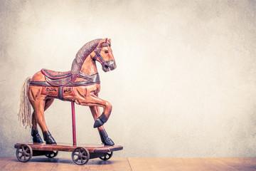 Vintage old antique Christmas wooden horse toy on wheels front concrete wall background. Holiday greeting card concept. Retro instagram style filtered photo