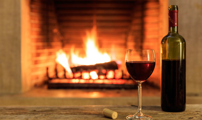 A glass and a bottle of red wine on burning fireplace background