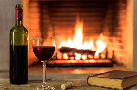 Red wine and a book on burning fireplace background