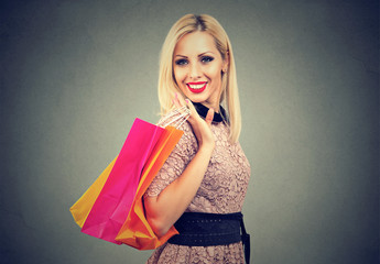Beautiful smiling fashion woman shopping holding  colorful bags isolated on gray background