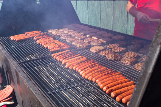Hot dogs and hamburgers on a smokey charcoal grill