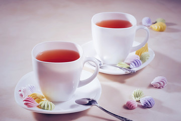 two white cups of tea with colorful meringue