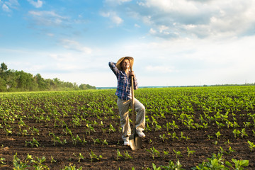 Happy small farmer with spade in spring field