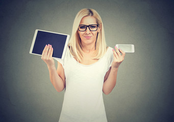 Perplexed woman in glasses shrugging shoulders uncertain what to choose tablet or smartphone