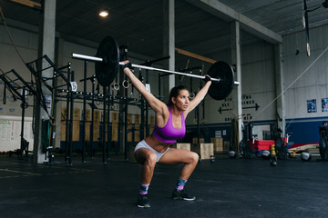 Determined sportswoman lifting heavy barbell
