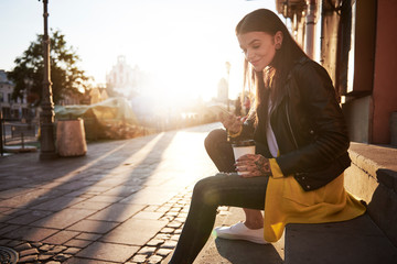 Young woman outdoors, holding coffee cup and smartphone, tattoos on hands