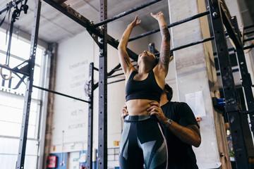 Trainer helping sportswoman in workout