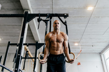 Muscular man training with flying rings