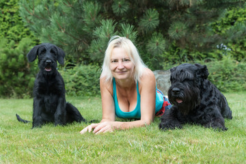 Smiling woman is lying between puppy and adult dog of Giant Black Schnauzer Dog