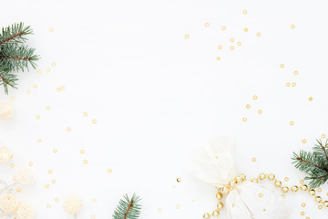 Bright Christmas composition with a gift & New Year decoration. Gold pearl beads, fir,  paper bag, garland and confetti on white. Flat lay. Winter holiday card
