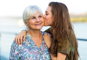 Young woman kissing her grandma