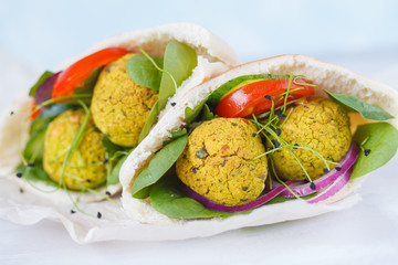 Baked falafel and fresh vegetables in pita bread, macro. Vegan dietary healthy food concept.