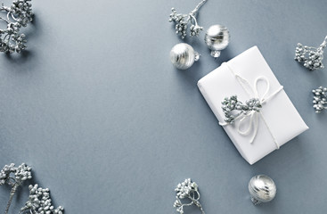 Silver Christmas Decorations and a Gift Box on Gray Background; flat lay arrangement