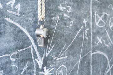 whistle of a soccer coach / referee on black board with strategy drawing