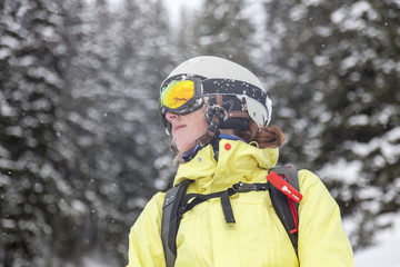 Austria, Kitzbuehel, woman with ski helmet and avalanche backpack in snow