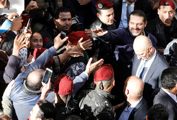Saad al-Hariri, who suspended his decision to resign as prime minister, gestures to his supporters at his home in Beirut