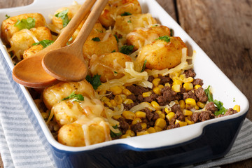 Homemade casserole of Tater Tots with minced beef, corn and cheese close-up in a baking dish. horizontal