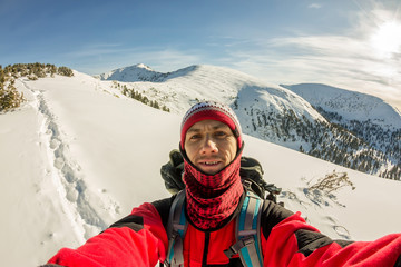 Selfi male traveler with a backpack in the winter mountains