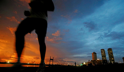 Financial district of Colombo is seen as a man runs along a path in front of the China invested Colombo Port City construction site in Colombo