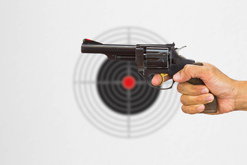 Hand holding black gun on blurred shooting target background