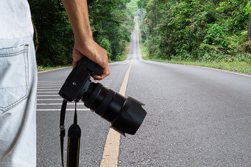 Man holding dslr digital camera on blurred straight road in national park background, photography hobby concept