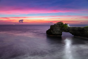 Pura Batu Bolong at dusk - temple on the rock near Tanah Lot in Bali, Indonesia. Pink sunset