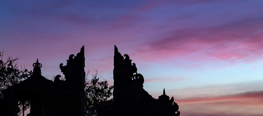 Wall Mural - Enjung Galuh Temple Silhouette at dusk. Pink sunset in Bali, Indonesia