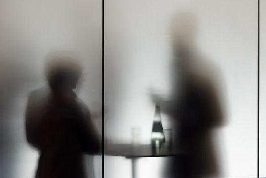 Konferenzteilnehmer machen eine Pause an einem Stehtisch hinter mattiertem Glas