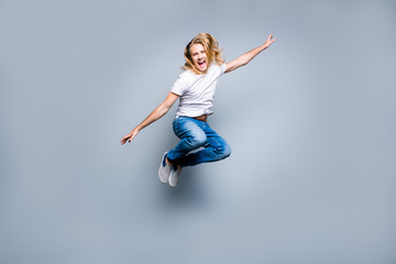 I'm trying to fly! Screaming smiling excited mad handsome hipster is celebrating and jumping up, isolated on grey background