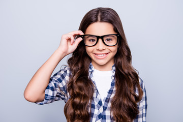 Closeup portrait of smart attractive little girl in checkered shirt  holding her spectacles  smiling looking to the camera standing over grey background