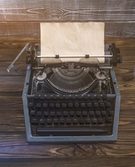 vintage typewriter with paper sheet on wood background. Space for your text, mock-up and simulations. Old thing