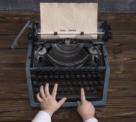 child's hand writing letter to Santa Claus on vintage typewriter in anticipation of the holiday of Christmas, new year. old paper with place for greeting