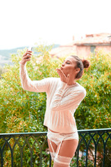 Beautiful young woman in white sweater and underwear, sending kiss to phone, standing on balcony. Tuscany, Italy. Small depth of field.