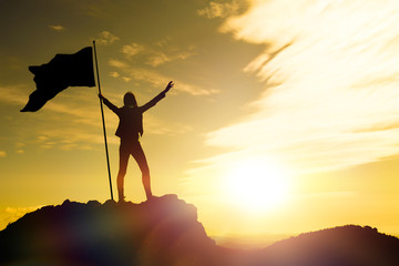 High achievement, silhouettes of the girl, flag of victory on the top of the mountain, hands up. A man on top of a mountain. Conceptual design. Against the dramatic sky with clouds at sunset. Fotobehang